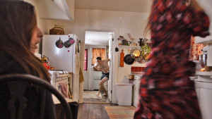 """Marcus (Matt Mercer) emerging from the bedroom chasing after Amandine (Karen Sours) while """"E"""" (Miriam Korn) watches"""